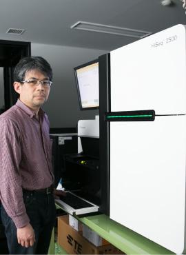 研究室が誇る最先端の解析装置「次世代シークエンサー」の前で。生物そのものや薬剤を扱うウェットな実験と、最先端装置を駆使したドライな解析の両輪で、生物の謎に迫る。