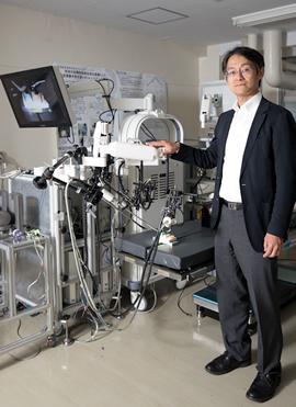 開発中の手術ロボットの前で。これまでの研究生活のすべてがここに詰まっていると言っても過言ではない。