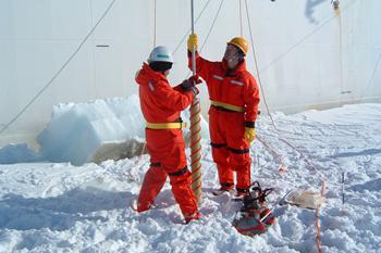 オホーツク海上の氷の上で、命綱を付けて観測を行う大島教授(右)。研究活動には長期のフィールドワークが必須だ。オホーツク海や南極など、極地の海を見て回る。現場で得たデータが、研究を推し進める大きな力となる。