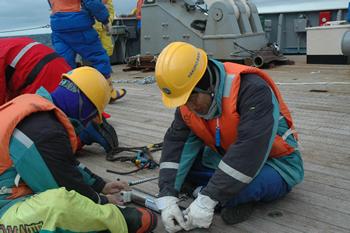 南極の観測船の甲板で手際よく測器のセッティングを行う。ケープダンレー付近の予定していた場所で係留ができず、急遽観測点を変更、測器のセッティングも変更して観測した結果が、底層水の流出の発見につながった。