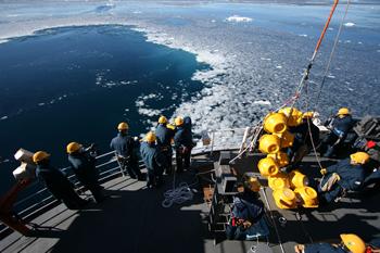 南極の厳しい環境のなかで観測作業に取り組む(日本南極観測隊「しらせ」にて)。海洋観測に欠かせない「係留系」を投入するところ。黄色の丸い部品は「係留系」の浮き。