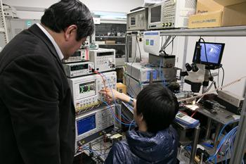 素子が発光するレーザ光の波形を見る小山教授と院生。