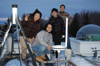 2012年2月22日、カナダ・アサバスカのオーロラ観測施設にて。塩川教授(最後列)以外の3名は大学院学生(一番左は韓国からの留学生、他は日本の学生)。ドームの中や左の装置はオーロラ観測のためのカメラや分光器。(塩川教授提供)