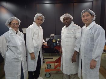 2013年10月17日、国立極地研究所の光学較正実験室にて。高感度全天カメラ(中央の装置)の較正実験の際に撮影。左より、エルサルバドルからの留学生(大学院学生)、塩川教授、ナイジェリアの研究者(大学講師)、韓国からの留学生(大学院学生)。各大学院生は2016年3月に名古屋大学で博士号取得。(塩川教授提供)