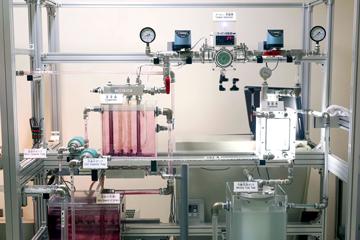 OTECのミニチュアモデルに見る「クローズドサイクル」の仕組み。ピンクに色付けされた温海水が蒸発器の水槽内に入り、チューブ内を流れる作動流体を温めて蒸気に変えタービンを回す。