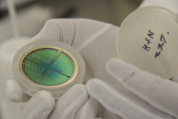 クリーンルームで製作した半導体ウェハー。コンパクトディスクやシャボン玉と同様、半導体それ自体には色がないが、超微細な構造のため表面に光の干渉が起こり、角度によってさまざまに光る。