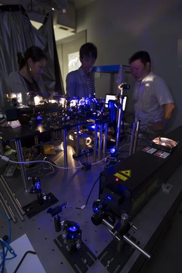 未来エレクトロニクス集積研究センター内で行われている、レーザー励起による窒化物半導体の発光特性評価(撮影のため、レーザーから目を守るために必要な保護メガネを外している。写真は名古屋大学提供)