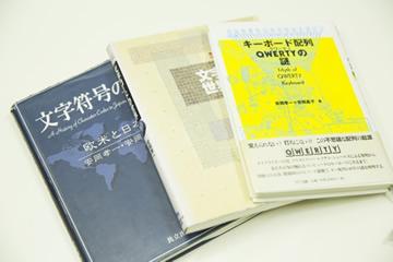 安岡教授の著作の一部。文字コードの歴史を扱った『文字符号の歴史』(安岡素子氏との共著)から、キーボード配列の謎に迫る『キーボード配列QWERTYの謎』(安岡素子氏との共著)など、文字コードを発端に広範なテーマを扱っている。