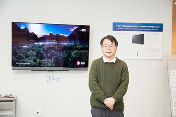 研究所を入ったところに掛けられている、IGZO-TFT搭載の65型有機ELテレビは、韓国LGディスプレイから寄贈されたものだ。