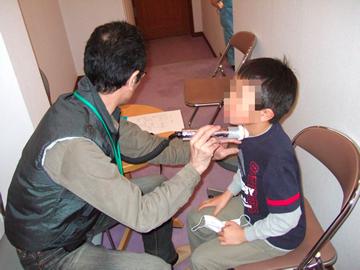 2011年3月に飯舘村で行われた子どもの甲状腺調査の様子。外部の放射線の影響を避けるため、空間線量の低い役場の通路で実施された