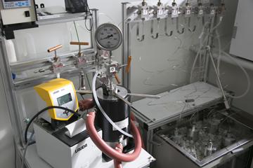 濃厚ポリマーブラシを厚膜化するために使われる高圧装置。テフロンの容器内に反応溶液と、ブラシを生やしたい部品を入れ、空気と接しないように密閉する。それを写真中央の高圧容器の中に入れ、水圧により高圧(たとえば5000気圧)をかけると、中の部品の表面には厚いブラシが生成される。