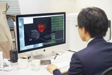 重田教授のデスク。画面に映るのはタンパク質の構造をモデル化したもの。