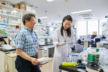 研究室で学生と談笑する清水教授。研究者たちの不断の取り組みが、最先端を切り拓いていく。