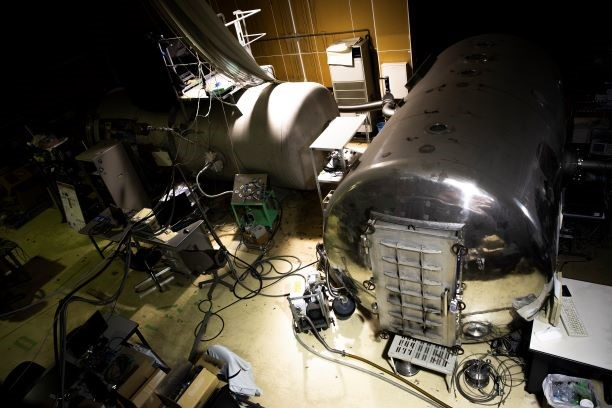 <左写真>東北大学流体科学研究所の高速流実験棟の中にある火星風洞は、火星のような低圧環境を生み出し、マッハ数、レイノルズ数を独立に制御できる世界唯一のもの。風洞そのものは、写真左奥の真空チャンバー(白い筒状のもの)の中にある。真空チャンバー内は、右手前のタンクで空気を吸い込むことで、火星同様の低圧環境になる。そのなかで、風洞に風を吹かせることによって火星に近い条件での実験が行える。