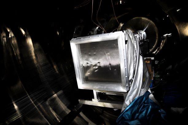 <右写真>真空チャンバーの内部。四角い枠の奥が風洞になっていて、この枠から空気を送る。枠にネットがついているのは、ごみを吸い込まないようにするのと、流れをきれいに整えるため。