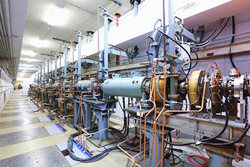 電子光理学研究センターの低エネルギー電子直線加速器。1967年建設。ここで発生・加速させた電子を、隣の部屋に設置された電子散乱施設において陽子に衝突させ、陽子半径を測定する。(写真提供 須田教授)