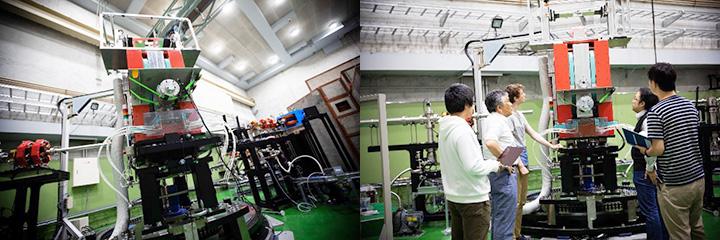 (左)東北大学電子光理学研究センターの第一実験室に設置された陽子半径の測定を行う新しいビームラインと散乱電子スペクトロメータ。低エネルギー電子直線加速器で加速された電子をここで陽子と衝突させる。散乱した電子を写真中央の赤い装置(スペクトロメータ)で捕獲し、散乱の様子を観測・測定する。測定の精度を高めるため、この赤い装置と同等の装置をもう一つ、これから設置するという(8月完成予定)。(右)この研究を担う助教や大学院生とともに。