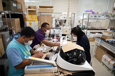 床次教授の研究室で、放射線の検出器を組み立てる海外からの留学生。「文字通り家内制手工業で、みんなが協力して手作りで一つひとつ検出器を組み立てています」